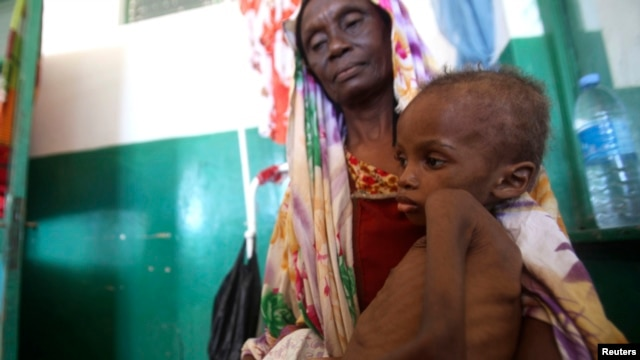 A Somali woman holds a malnourished child as they wait for medical attention at Banadir hospital in Mogadishu, April 28, 2014.