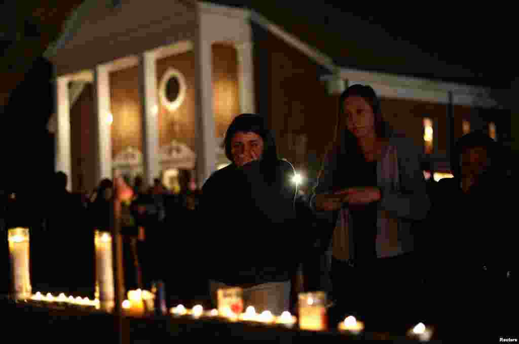 A woman covers her mouth as others look on stand near candles outside Saint Rose of Lima Roman Catholic Church near Sandy Hook Elementary School on Dec. 14, 2012.