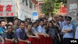 被隔离在济南法院警戒线外面的民众。2013年8月22日(美国之音东方拍摄)