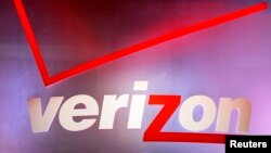 FILE - A Verizon sign is seen displayed at an electronics show.