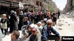 FILE - Residents await food aid distributed by the U.N. refugee agency at the Palestinian refugee camp of Yarmouk, south of Damascus, Syria, May 2014.
