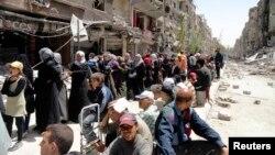 Warga menunggu bantuan makanan yang didistribusikan oleh lembaga pengungsi PBBdi kamp pengungsi di Yarmouk, bagian selatan Damaskus, Suriah.