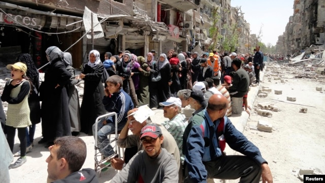 FILE - Residents wait to receive food aid distributed by the U.N. refugee agency at the Palestinian refugee camp of Yarmouk, south of Damascus, Syria, May 2014.