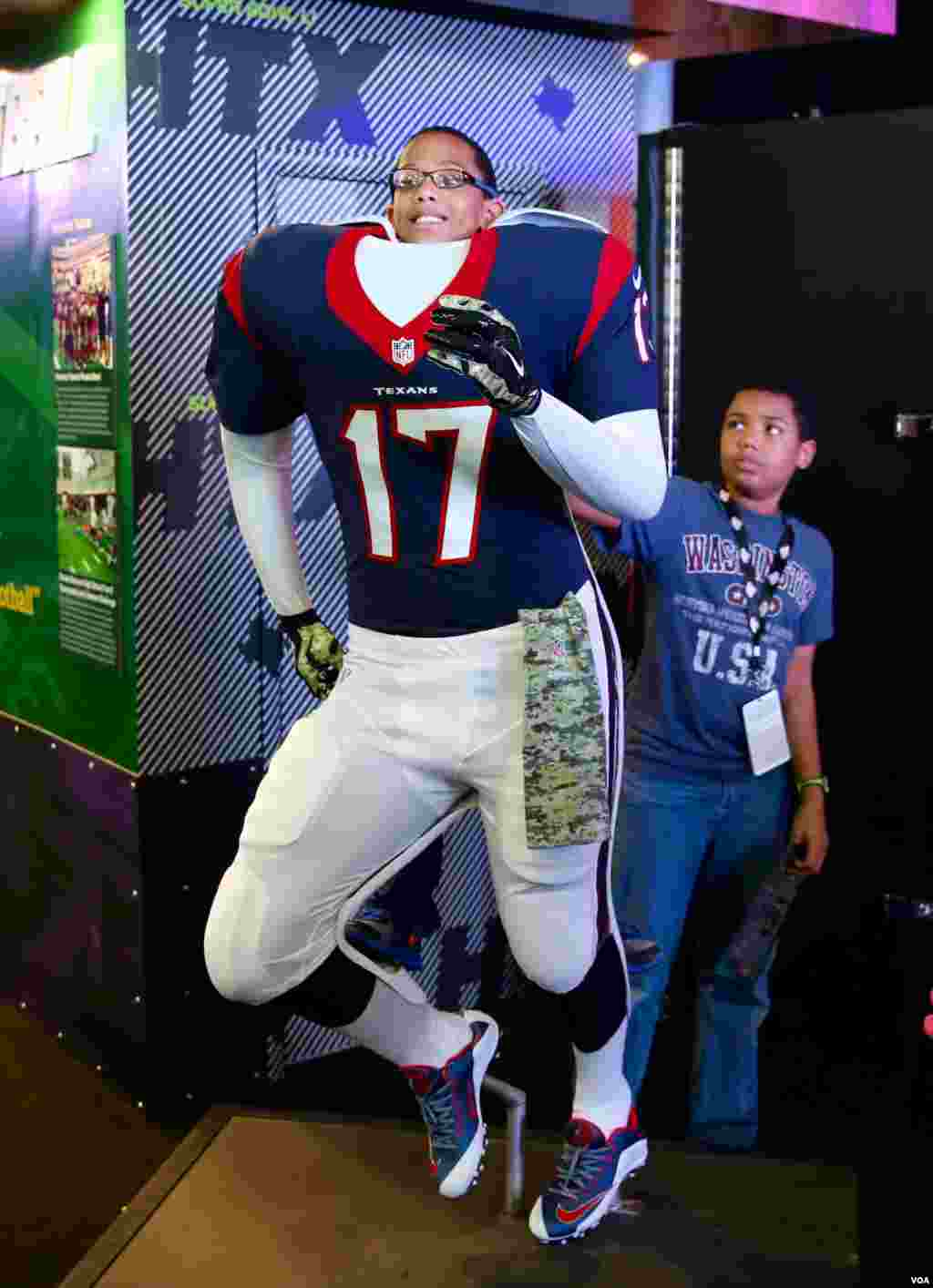 A young fan pretends to be a player on his favorite team, the Houston Texans, at the NFL Experience in downtown Houston. The Super Bowl, the NFL championship game and most watched football game worldwide, will be played here on Sunday, February 5th. (B. A