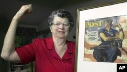 "FILE - Mary Doyle Keefe poses at her home in Nashua, New Hampshire, with the May 29, 1943, cover of the ""Saturday Evening Post"" for which she had modeled as ""Rosie the Riveter"" in a Norman Rockwell painting, May 22, 2002."