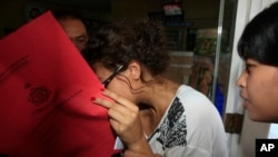Heather Mack, menutupi wajahnya, dibawa polisi terkait pembunuhan ibunya Sheila von Wiese-Mack di Bali (15/8). (AP/Firdia Lisnawati)