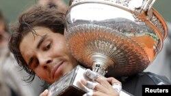 El tenista español Rafa Nadal sostiene su trofeo de campeón del Abierto de Francia, conquistado tras derrotar al serbio Novak Djokovic en la final de Roland Garros.
