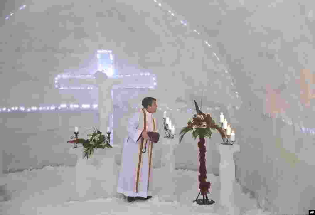 A Romanian priest puts out candles inside a church built entirely from ice blocks cut from a frozen lake after a blessing religious service at the Balea Lac resort in the Fagaras mountains.