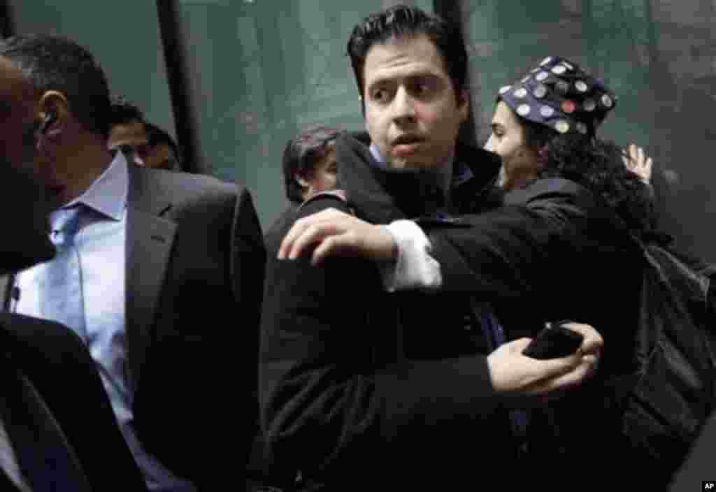Демонстрант се обидува да попречи минувач во близина на Њујоршката берза. (AP Photo/Seth Wenig)
