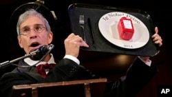 Master of Ceremonies Marc Abrahams holds up the 2014 Ig Nobel Prize trophy during a performance at the Ig Nobel Prize ceremony at Harvard University, in Cambridge, Mass., Sept. 18, 2014.