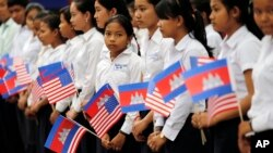 FILE PHOTO - Students from a local high school carry the U.S. national flags and Cambodia's national flags in Siem Reap, Cambodia, Saturday, March 21, 2015. (AP Photo/Wong Maye-E)