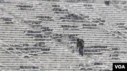 Un obrero limpia las gradas cubiertas de nieve en un estadio de fútbol en Pennsylvania.