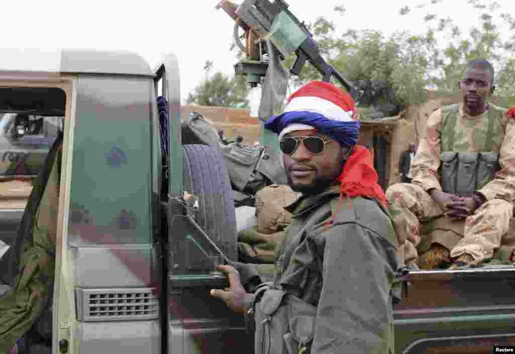 Un soldat malien arborant un drapeau français se tient près d'un véhicule récemment capturé à Gao.