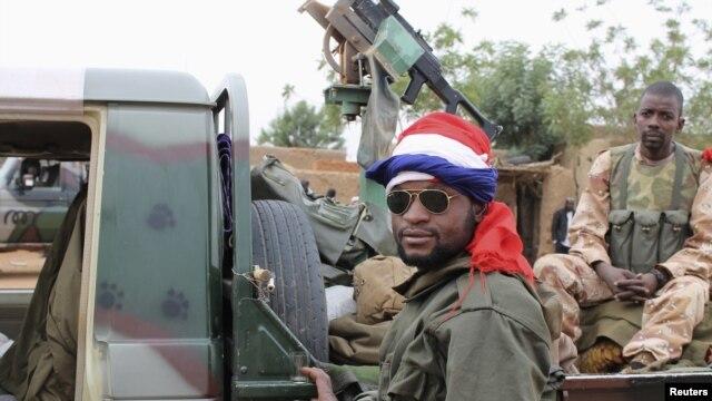 Binh sĩ Mali với cờ Pháp quấn quanh đầu đứng cạnh một chiếc xe quân sự tại thị trấn Gao.