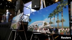 Los Angeles Rams Chief Operating Officer Kevin Demoff speaks behind an illustration of the Rams' planned new stadium at a celebration to welcome NFL team, the Los Angeles Rams, at the Forum in Inglewood, California, Jan. 15, 2016.
