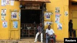Des hommes assis devant des affiches électorales à Beni, dans la province du Nord-Kivu en RDC, le 5 décembre 2018.