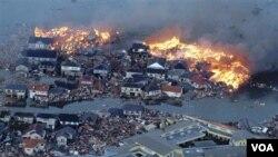 Rumah-rumah terbakar sementara sungai Natori meluap setelah tsunami melanda kota Natori, provinsi Miyagi, Jepang timur laut, Jumat (11/3).
