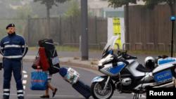 En la imagen, una mujer con pertenencias pasa junto a un policía durante la evacuación de unas 60.000 personas en Fráncfort, el 3 de septiembre de 2017.