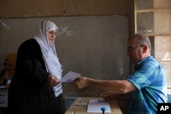 A woman receive a voting bill at a polling station as Kurds vote for independence in the disputed city of Kirkuk, Sept. 25, 2017. Iraq's Kurdish region vote in a referendum on whether to secede from Iraq.