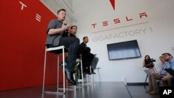FILE - Elon Musk, CEO of Tesla Motors Inc., left, discusses the company's new Gigafactory in Sparks, Nevada, July 26, 2016. Tesla announced in September that it had been selected to build a battery storage project at the Mira Loma electricity substation in California's Riverside County.