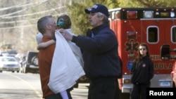 Một bé gái được đưa ra khỏi trường tiểu học Sandy Hook sau vụ nổ súng.