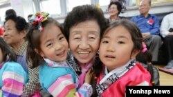 서울의 한 어린이집 원아들이 8일 어버이날을 맞아 주변 경로당 어른신들께 노래와 율동을 선보인 후 기념촬영을 하고 있다.