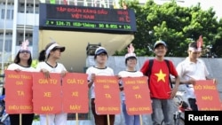 Students hold placards in a protest against a gasoline price hike in front of Petrolimex, in Hanoi, September 16, 2012.