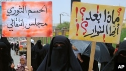 Yemeni anti-government demonstrators holds placards during a protest under the slogan 'Friday of a Civil State' in Sana'a , July 15, 2011