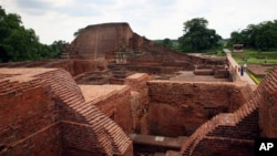 FILE - Tourists walk at the ruins of the Nalanda University at Nalanda, India, July 5, 2006.