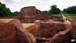 FILE - Tourists walk at the ruins of the Nalanda University at Nalanda, India, July 5, 2006.