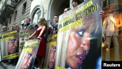 FILE - PETA (People for the Ethical Treatment of Animals) protestors hold banners depicting Italian designer Donatella Versace in front of the Versace store in Milan, Italy.