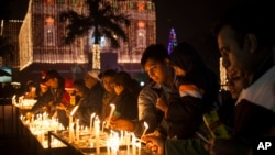 FILE - Indian Christians light candles at a Sacred Heart Cathedral on the eve of Christmas in New Delhi, India, Wednesday, Dec. 24, 2014.