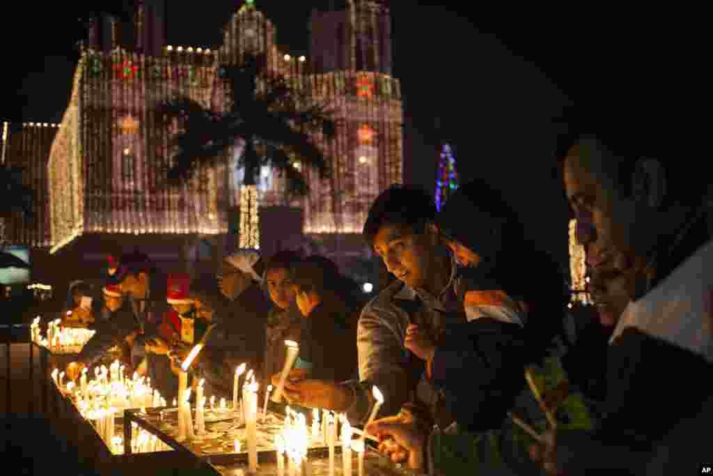 Des chrétiens indiens allument des bougies dans une cathédrale Sacré-Cœur à la veille de Noël à New Delhi, en Inde, mercredi 24 décembre, 2014. Noël est une fête nationale en Inde.