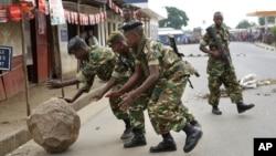 Des soldats roulent un roc placé par des manifestants à Cibitoke, un quartire de Bujumbura, Burundi, vendredi 22 mai 2015.