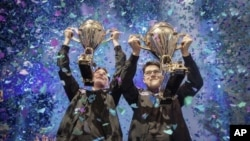 "In this Saturday, July 27, 2019 photo, provided by Epic Games, Emil ""Nyhrox"" Bergquist Pedersen, of Norway, left, and David ""Aqua"" Wang, of Austria, hold up their trophies after winning the Fortnite World Cup duo championship in New York. (Epic Games via"