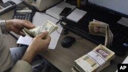 Nhân viên của một văn phòng đổi tiền đếm đôla, trên bàn là một xấp giấy bac Iran