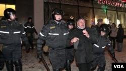 Polisi anti huru-hara menangkap seorang demonstran di Minsk, Belarusia.