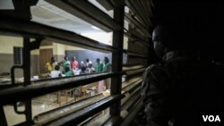 A man looks through a window as votes are about to be tallied at a polling station in Ouagadougou, Burkina Faso, November 29, 2015. (Photo - E. Iob/VOA)