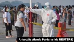 Seorang petugas yang mengenakan alat pelindung memeriksa suhu pekerja migran Indonesia yang tiba dari Malaysia selama karantina untuk mencegah penyebaran COVID-19, sebelum berolahraga di pangkalan udara Soewondo di Medan, Provinsi Sumatra Utara, 11 April 2020.
