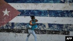 In this file photo taken on June 22, 2021 a woman walks near a wall depicting the Cuban flag in Havana. (Photo: AFP)