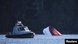 An RCMP boat carrying divers sits beside a capsized whale watching boat in Tofino, British Columbia, Oct. 26, 2015. A tour boat with 27 passengers on board sank off the coast of British Columbia Sunday.