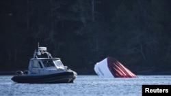 Un bote de la Policía canadiense lleva buzos hasta el lugar donde se hundió el domingo un barco crucero en Tofino, en la Columbia Británica.