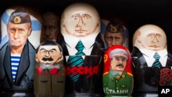 FILE - Russian traditional wooden matryoshka dolls showing Russian President Vladimir Putin and Soviet leader Joseph Stalin, front, are on sale in a street souvenir shop in Moscow, Dec. 2, 2015.