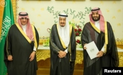 FILE - (L-R) Saudi Crown Prince Mohammed bin Nayef, Saudi King Salman, and Saudi Arabia's Deputy Crown Prince Mohammed bin Salman stand together as Saudi Arabia's Cabinet agrees to implement a broad reform plan known as Vision 2030 in Riyadh, April 25, 2016.