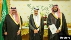FILE - (L-R) Saudi Crown Prince Mohammed bin Nayef, Saudi King Salman, and Saudi Arabia's Deputy Crown Prince Mohammed bin Salman stand together as Saudi Arabia's cabinet agrees to implement a broad reform plan.