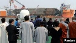 Para anggota keluarga korban tenggelamnya kapal Sewol mengamati upacara pengangkatan lkapal tersebut dari dasat laut Jindo, Korea Selatan, 28 Maret 2017 (Foto: Yonhap via Reuters).