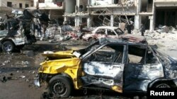 People inspect the site of a two bomb blasts in the mostly government-controlled city of Homs, Syria, in this handout picture provided by SANA on Feb 21, 2016.