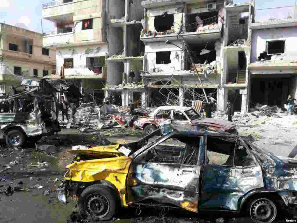 People inspect the site of a double bomb attack in the government-controlled city of Homs, Syria, in this handout picture provided by SANA.