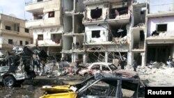 Warga setempat memeriksa lokasi ledakan bom di Homs, Suriah hari Minggu (21/2).