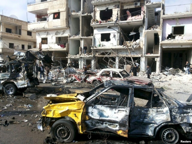 People inspect the site of a two bomb blasts in the government-controlled city of Homs, Syria, in this handout picture provided by SANA on Feb. 21, 2016.